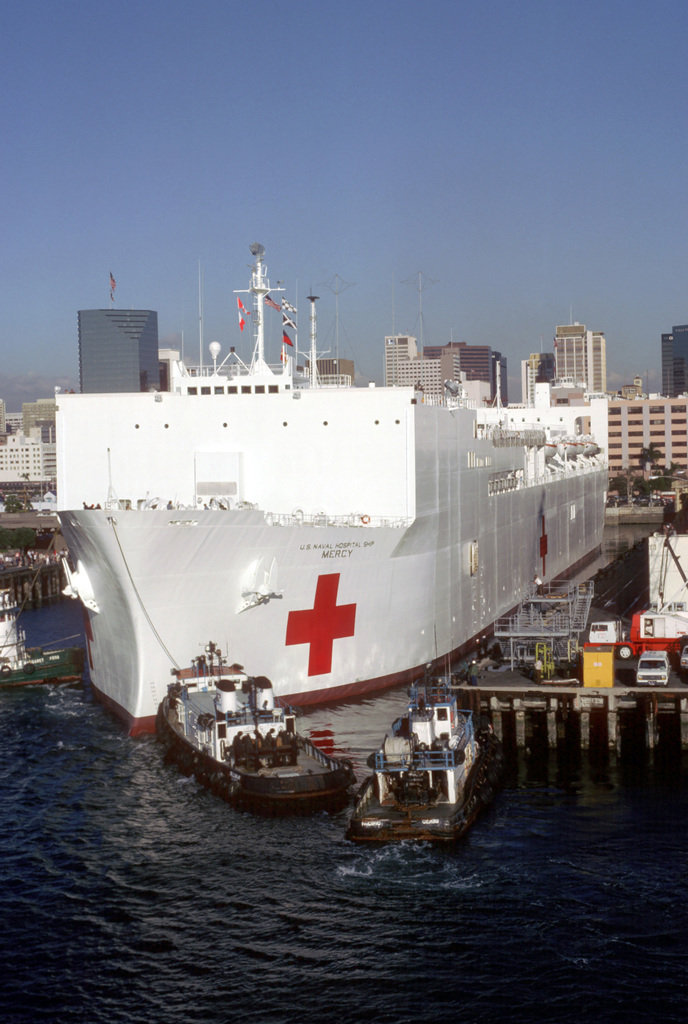 Tugboats assist the hospital ship USNS MERCY (T-AH 19) away from a pier at the Naval Supply Center as the ship gets underway on its maiden voyage to the islands of the Western Pacific