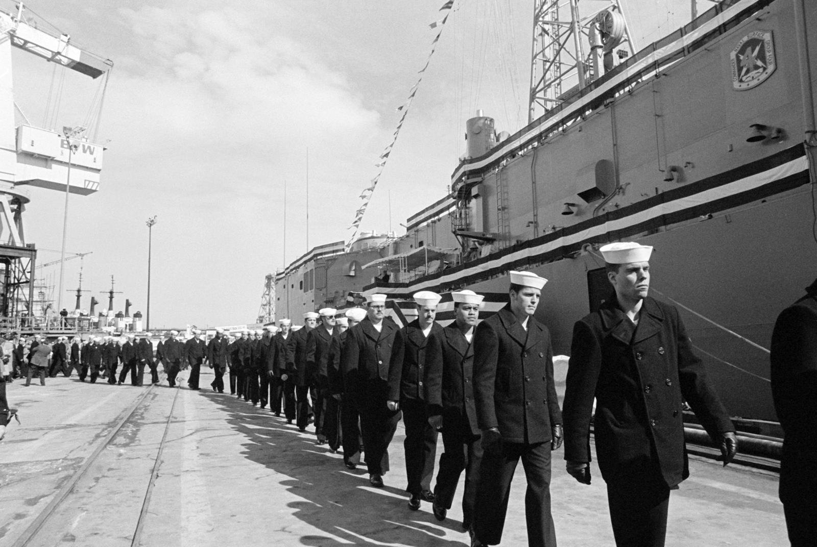 Crew members go aboard the ship in single file during the commissioning of the guided missile frigate USS KAUFFMAN (FFG 59)