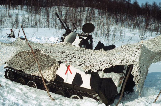 A camouflaged Norwegian NM-135 armored personnel carrier equipped with a 20 mm cannon is postioned in the field during Exercise COLD WINTER'87