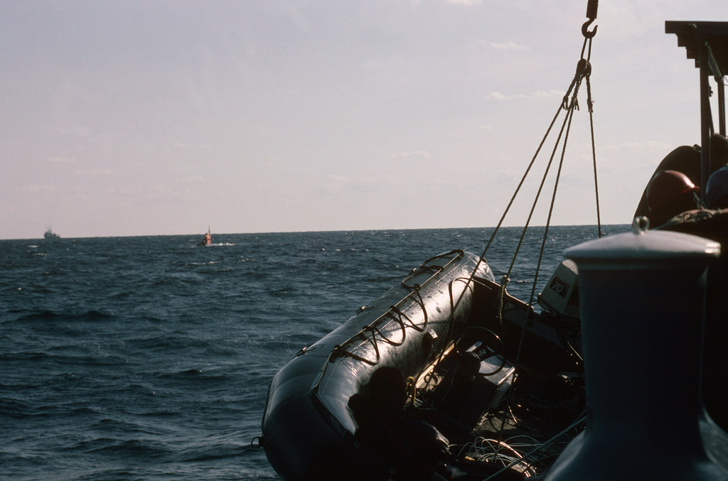 A diver relaxes in a Zodiac boat being hoisted aboard the Submarine Rescue Ship USS SUNBIRD (ASR 15) after a personnel transfer with the nuclear-powered research submersible NR-1, background