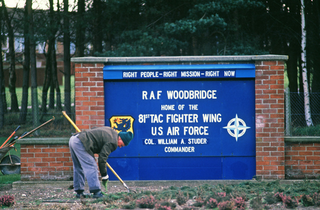 A ground maintenance man weeds the area in front of the sign at the entrance to RAF WOODBRIDGE, HOME OF THE 81ST TACTICAL FIGHTER WING.  The wing is preparing for deployment to Zaragoza Air Base, Spain, for weapons tactics training
