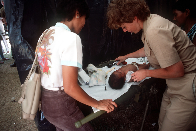 A medical officer from the hospital ship USNS MERCY (T-AH-19) examines an infant while participating in a medical civic action program for local Filipinos