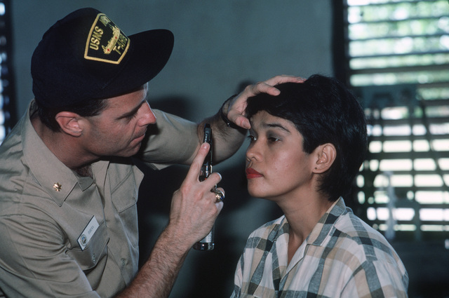 A medical officer from the hospital ship USNS MERCY (T-AH 19) performs an examination while participating in a medical civic action program for local Filipinos