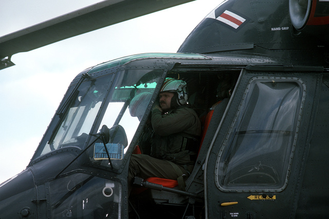 A pilot straps his helmet on prior to taking off from the guided missile frigate USS SIDES (FFG-14) in a Helicopter Light Anti-submarine Squadron 84 (HSL-84) SH-2F Sea Sprite helicopter