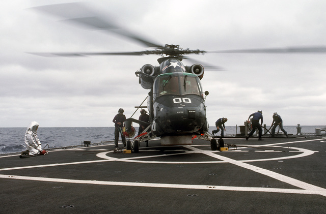 Crew members remove fuel hoses from the helicopter pad of the guided missile frigate USS SIDES (FFG 14) after refueling a Helicopter Light Anti-submarine Squadron 84 (HSL-84) SH-2F Sea Sprite helicopter.  A firefighter stands by in a proximity suit