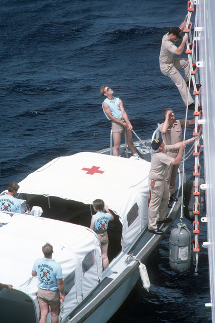 Passengers use a rope ladder to disembark from a motor launch moored alongside the hospital ship USNS MERCY (T-AH 19)