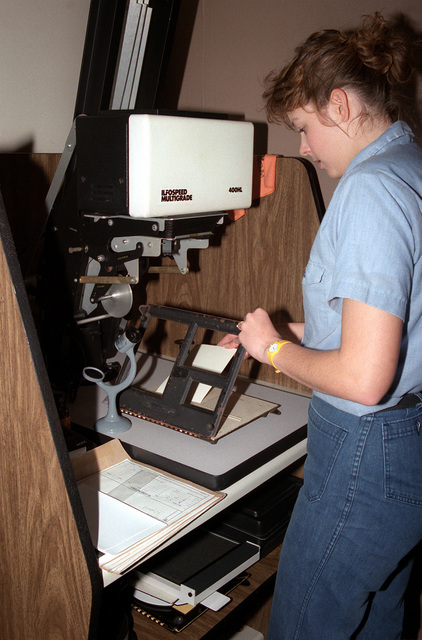 Photographer's Mate AIRMAN Michelle Quinn readies an enlarger before making a set of black and white prints in a darkroom at the Fleet Imaging Center facility