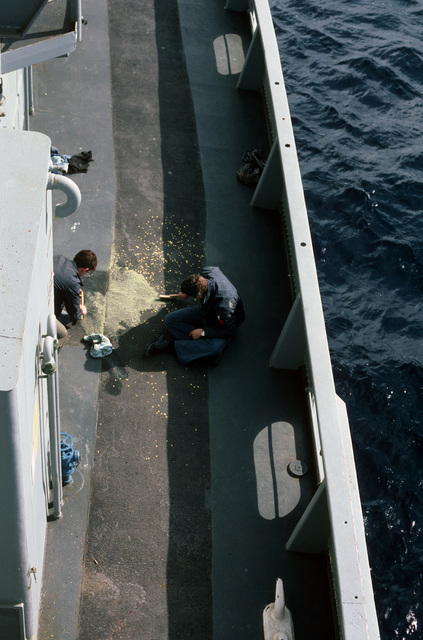Two crewman use wire brushes to clean up spilled paint from the deck of the submarine rescue ship USS SUNBIRD (ASR 15)