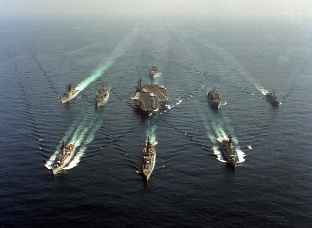 An aerial bow view of the aircraft carrier USS KITTY HAWK (CV-63) and its battle group underway. The ships are, first row, left to right: frigate USS STEIN (FF-1065), guided missile cruiser HALSEY (CG-23) frigate USS BARBEY (FF-1088); second row: guided missile destroyer USS CALLAGHAN (DDG-994), ammunition ship USS MOUNT HOOD (AE-29), KITTY HAWK, combat stores ship USS MARS (AFS-1), and the guided missile frigate USS VANDEGRIFT (FFG-48). The fleet oiler USS WILLAMETTE (AO-180) follows