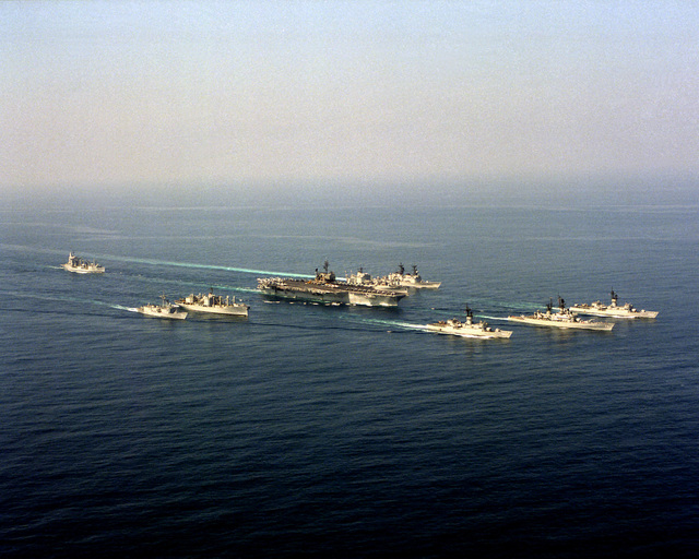 An aerial starboard bow view of the aircraft carrier USS KITTY HAWK (CV-63) and its battle group underway. The ships are, left to right: fleet oiler USS WILLIAMETTE (AO-180), guided missile destroyer USS CALLAGHAN (DDG-994), ammunition ship USS MOUNT HOOD (AE-29), KITTY HAWK, combat stores ship USS MARS (AFS-1), guided missile frigate USS VANDEGRIFT (FFG-48), frigate USS STEIN (FF-1065), guided missile cruiser USS HALSEY (CG-23) and frigate USS BARBEY (FF-1088)