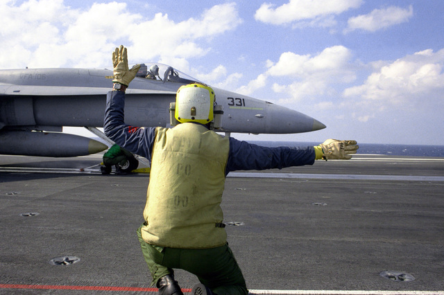 A flight deck crew member signals to the pilot of an F/A-18 Hornet aircraft readied for launch aboard the nuclear-powered aircraft carrier USS THEODORE ROOSEVELT (CVN-71)