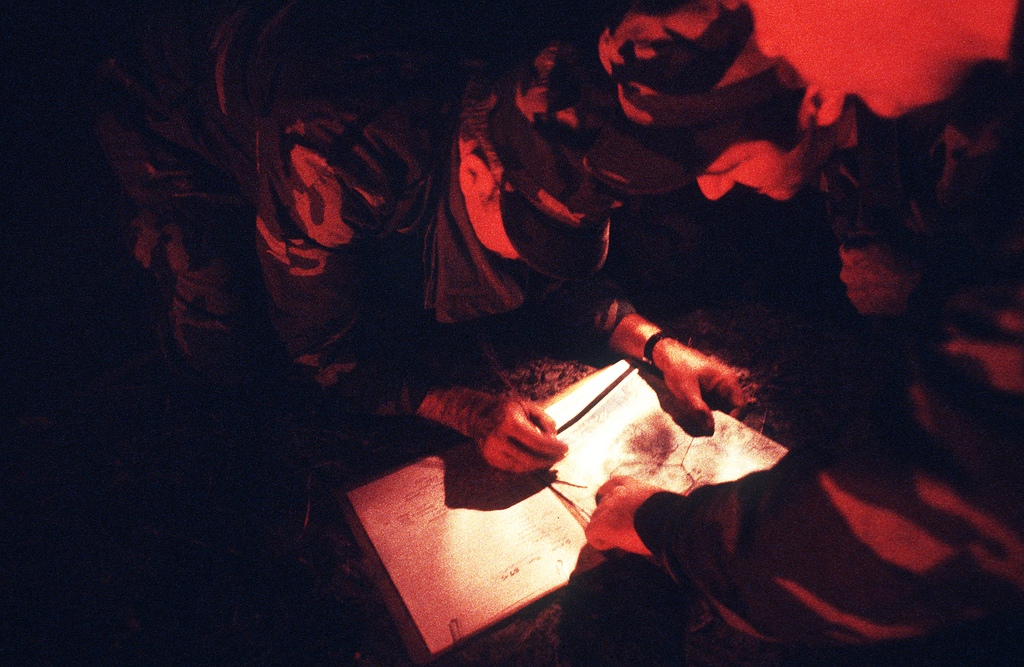 Members of the 16th Special Operations Squadron (SOS) plan aggressor strategy during a joint-service escape and evasion field training exercise at Outlying Field Choctaw