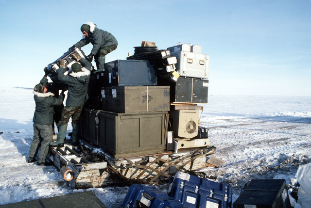 Members of the 5th Combat Information Systems Group unload supplies needed to make the tactical air navigation (TACAN) system operational.  The men are participating in Exercise COBBLER FREEZE'87, a cold-weather force projection exercise conducted by the Alaskan Air Command