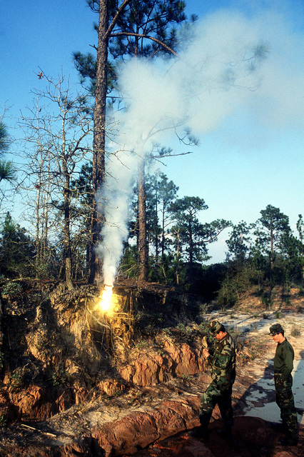 SSGT Tom Hatch, 16th Special Operations Squadron, conducts an M-49 surface trip flare demonstration at the aggressor forces base camp during a joint-service escape and evasion field training exercise at Outlying Field Choctaw