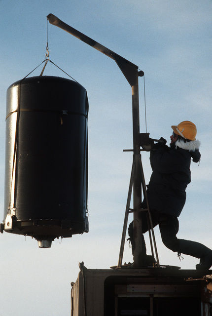 STAFF Sergeant (SSGT) Andy Neitzel, 5th Combat Information Systems Group, uses a small crane to hoist a radar dome onto the top of a tactical air navigation (TACAN) system van.  He is participating in Exercise COBBLER FREEZE'87, a cold-weather force projection exercise conducted by the Alaskan Air Command