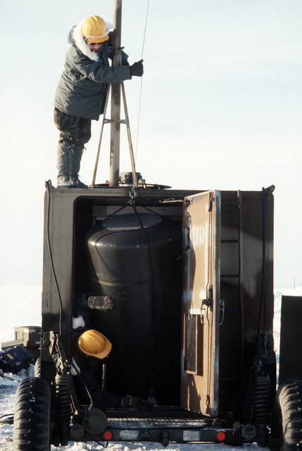 STAFF Sergeant (SSGT) Andy Neitzel and SSGT Steve Yeater, both of the 5th Combat Information Systems Group, remove a radar dome from inside a tactical air navigation (TACAN) system van.  The men are participating in Exercise COBBLER FREEZE'87, a cold-weather force projection exercise conducted by the Alaskan Air Command