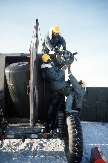 STAFF Sergeant (SSGT) Andy Neitzel, Technical Sergeant (TSGT) Harry Jones and SSGT Steve Yeater, all of the 5th Combat Information Systems Group, hoist a plate used to anchor a radar dome to the top of a tactical air navigation (TACAN) system van.  The men are participating in Exercise COBBLER FREEZE'87, a cold-weather force projection exercise conducted by the Alaskan Air Command