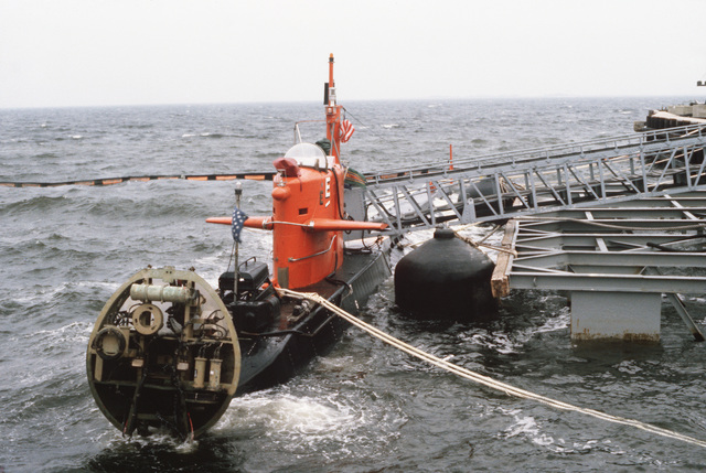 The nuclear-powered research submersible NR-1 moored in port with hinged bow lifted showing lighting ballast for strobes.  The submersible was forced to return to port when a storm hampered diving operations
