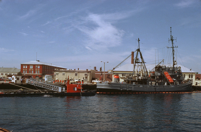A starboard quarter view of the submarine rescue ship USS SUNBIRD (ASR 15) and the nuclear-powered research submersible NR-1 tied up in port after operations in the Gulf of Mexico