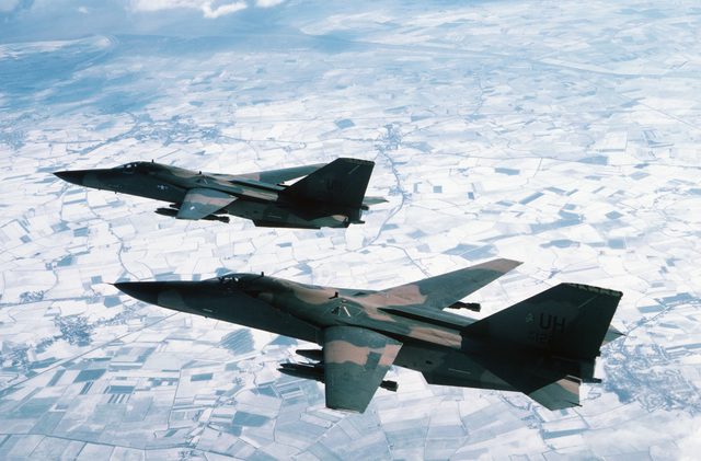 An air-to-air left side view of two 79th Tactical Squadron F-111E Aardvarck aircraft in formation over central England while en route to a bombing range in northern Scotland