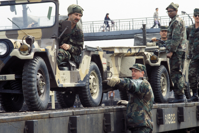 Staff Sergeant (SSG) James Mulligan, 25th Transportation Company, directs the unloading of M151 light vehicles from a rail car during the joint US/South Korean Exercise TEAM SPIRIT '87