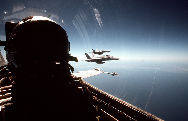 """A self-portrait of Commander J. """"Flamo"""" Fleming of Strike Fighter Squadron 132 (VFA-132) as he pilots his F/A-18A Hornet aircraft on a flight out of Naval Air Station, Cecil Field, Florida. Flying off Fleming's wing are two other VFA-132 F/A-18A Hornet aircraft"""