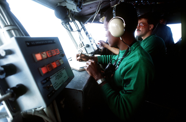 In the flight operations center aboard the Auxiliary Aircraft Landing Training Ship USS LEXINGTON (AVT 16), a petty officer makes an entry on a log sheet as he observes the activities in progress on the flight deck during pilot carrier training in the Gulf of Mexico