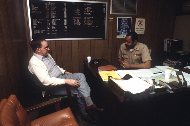 LT. Northington, administrative legal officer at the Naval Communication Area MASTER Station, Atlantic, converses with a visitor in his office