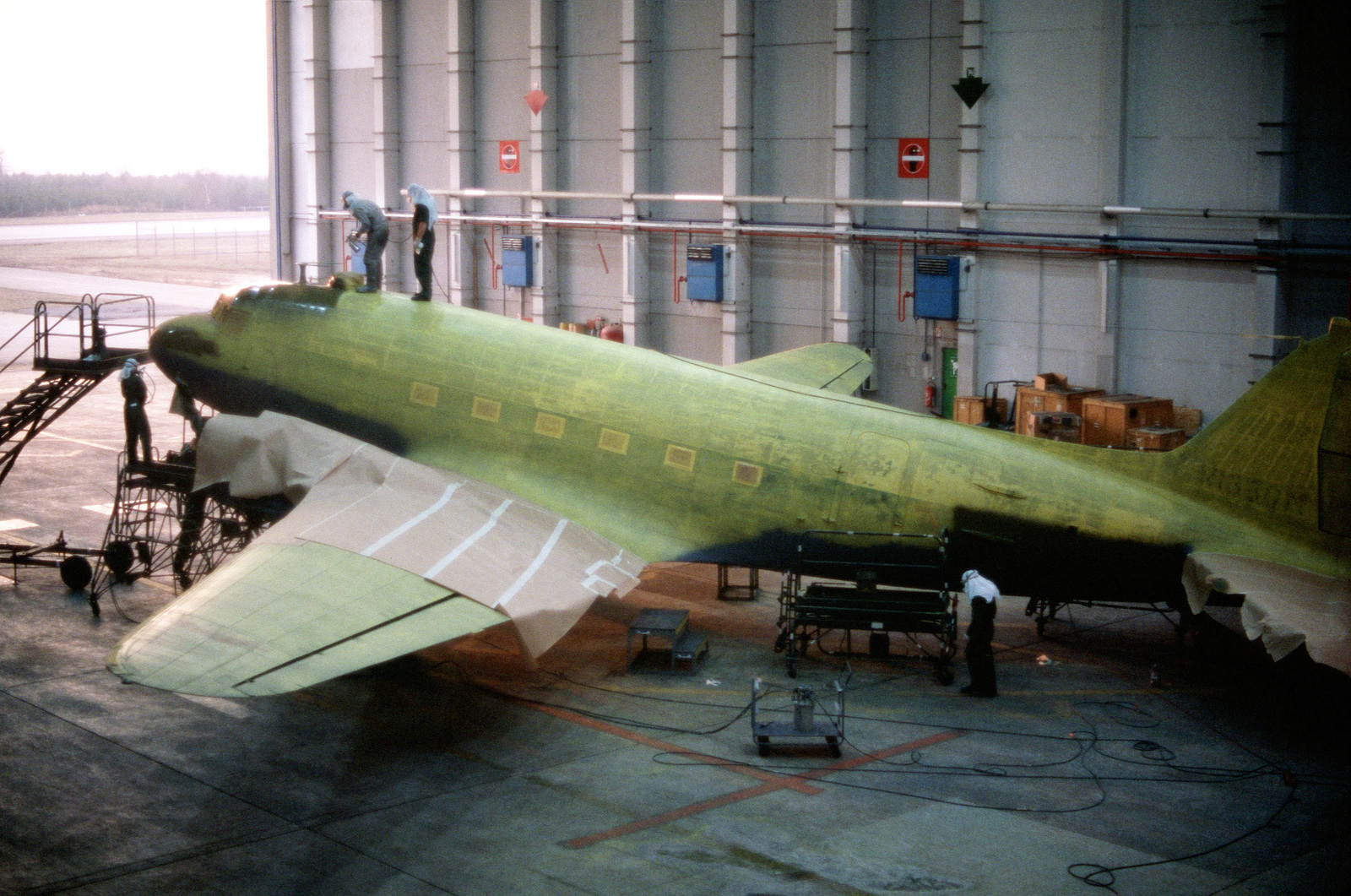 Members of the 435th Organizational Maintenance Squadron and the 435th Field Maintenance Squadron paint a C-47 Skytrain aircraft.  The historic Skytrain, which played a vital supply role during the Berlin Airlift of 1948-1949, is undergoing restoration fo