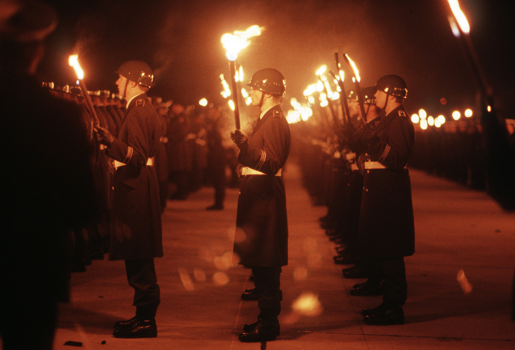 "Members of the German military carry lit torches in honor of General (GEN) Charles L. Donnelly Jr., departing commander in chief, US Air Force Europe, and Allied Air Forces Central Europe. The Soldiers are participating in the""Grand Tatoo,""one of the West Germany military's highest honors"