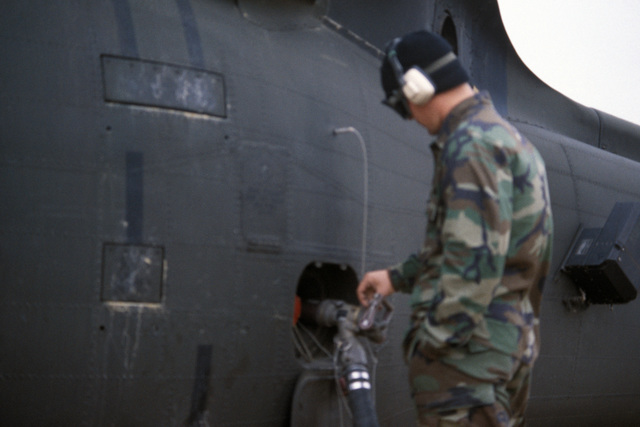 Specialist Fourth Class (SPC) Byron Hill, 854th Supply and Service Company Utah National Guard, refuels a UH-60 Black Hawk (Blackhawk) helicopter at a refueling point during the joint US/South Korean Exercise TEAM SPIRIT '87