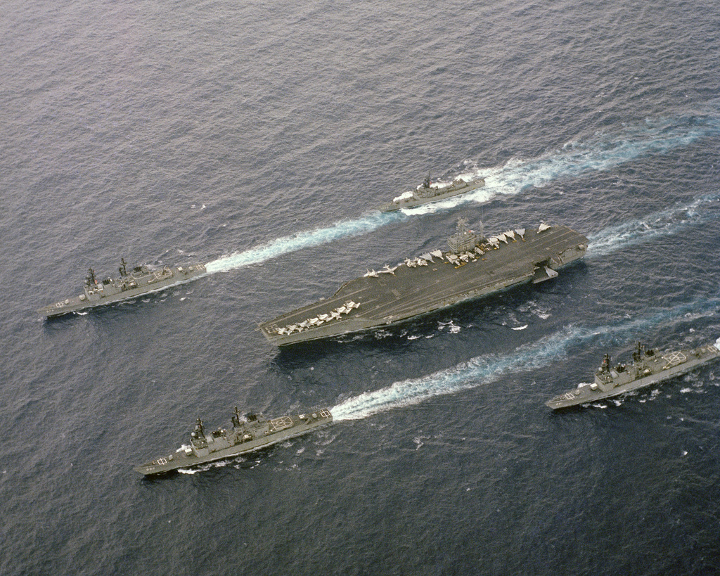 An elevated port bow view of the nuclear-powered aircraft carrier USS DWIGHT D. EISENHOWER (CVN 69), underway. Escorting the EISENHOWER are, clockwise from upper left, the destroyer USS COMPTE DE GRASSE (DD 974), the frigate USS GARCIA (FF 1040, and the destroyers USS JOHN HANCOCK (DD 981) and USS NICHOLSON (DD 982)