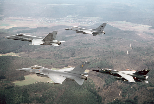 An air-to-air left side view of a Canadian CF-18 aircraft leading a Belgian Air Force F-16 aircraft, a Royal Netherlands Air Force F-16 aircraft and a French Mirage F-1 aircraft.  These aircraft are part of a larger, 15-aircraft formation taking part in a
