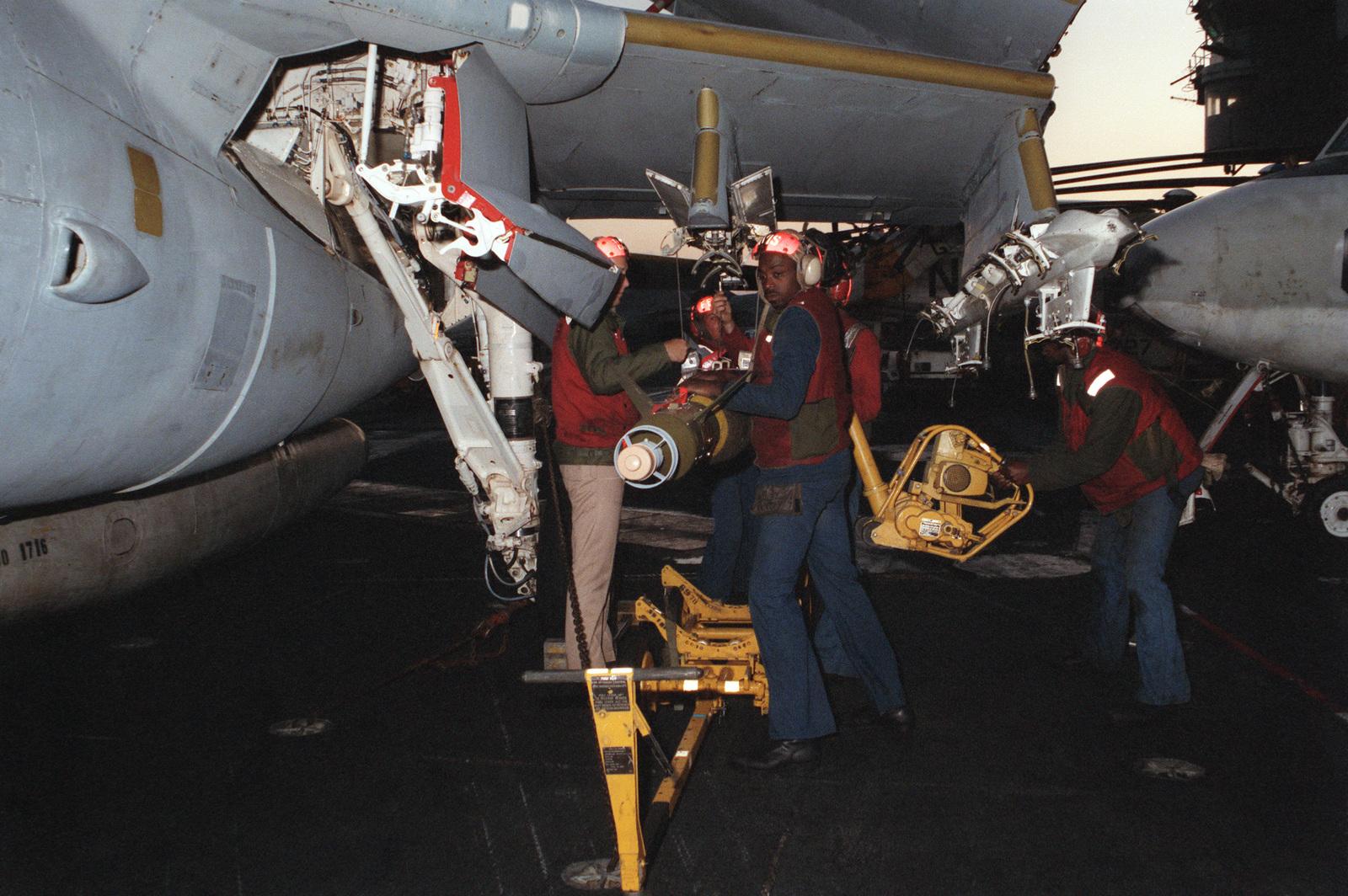 Aviation ordnancemen load a laser-guided bomb onto the wing pylon of an A-6E Intruder aircraft aboard the nuclear-powered aircraft carrier USS DWIGHT D. EISENHOWER (CVN 69)