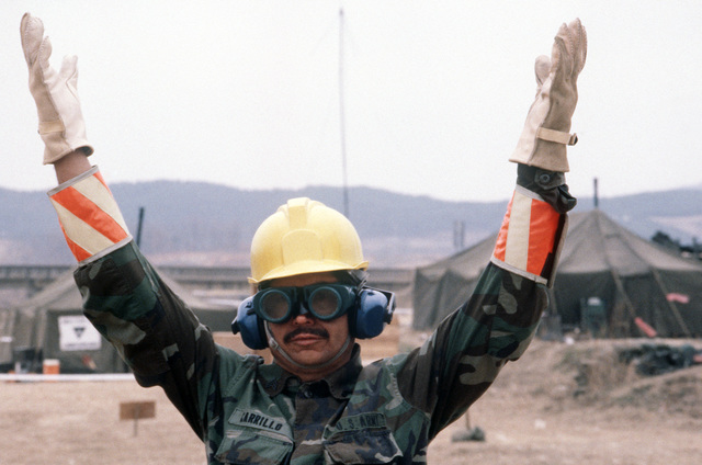Sergeant (SGT) Ernesto Carrillo, 2221st Quartermaster Company, uses hand signals to guide a helicopter into a refueling point during the joint US/South Korean Exercise TEAM SPIRIT '87