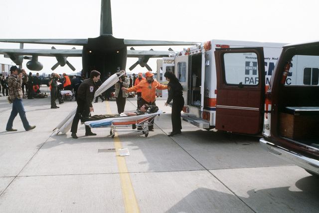 Simulated casualties are removed from a C-130 Hercules aircraft and placed into ambulances on the flight line during the National Disaster Medical System exercise