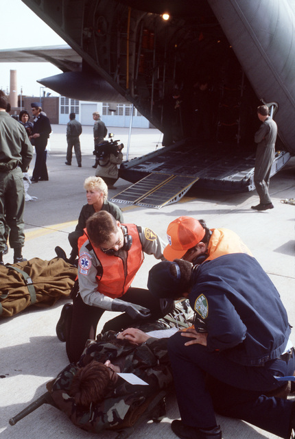 Simulated casualties are removed from a C-130 Hercules aircraft and treated on the flight line during the National Disaster Medical System exercise