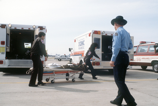 Simulated casualties are removed from ambulances on the flight line during the National Disaster Medical System exercise