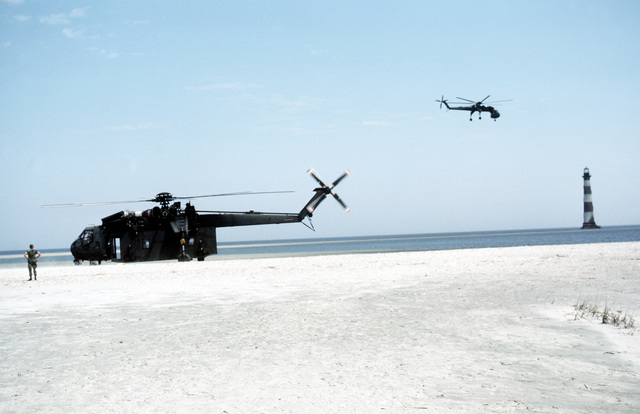 A CH-54 Tahre helicopter awaits loading while parked on the landing zone as another CH-54 flies by. The helicopters are being used during a Marine Corps Reserve weekend training exercise