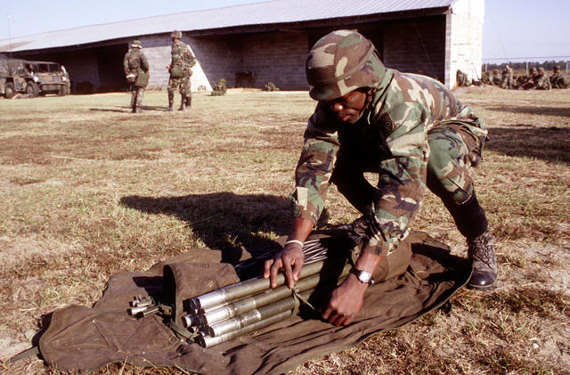 SGT. Lezar Christie, Company A, 82nd Airborne Division, places camouflage poles in a carrying case during a joint Air Force and Army air-drop/air-assault exercise