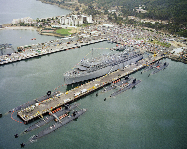 An aerial port bow view of the Submarine Tender USS DIXON (AS 37) and various submarines tied up alongside the ship and piers