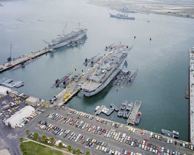An aerial starboard quarter view of the Submarine Tenders USS DIXON (AS 37), foreground, and USS MCKEE (AS 41), background, and various submarines tied up alongside the ship and piers