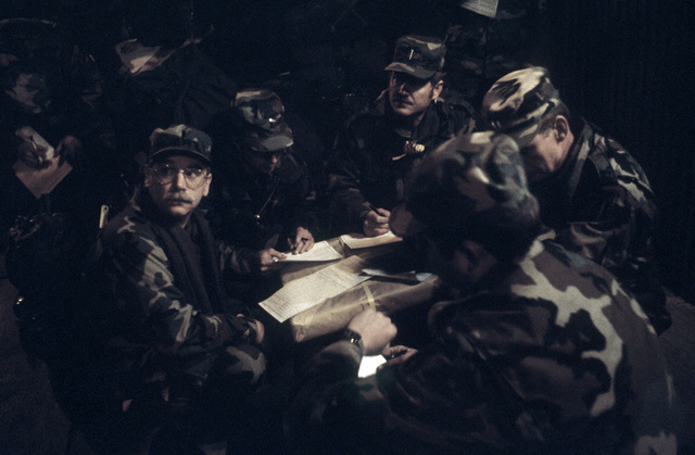 National Guardsmen fill out customs forms under the sodium vapor lights in the command post area at the conclusion of the joint US/South Korean Exercise TEAM SPIRIT '87