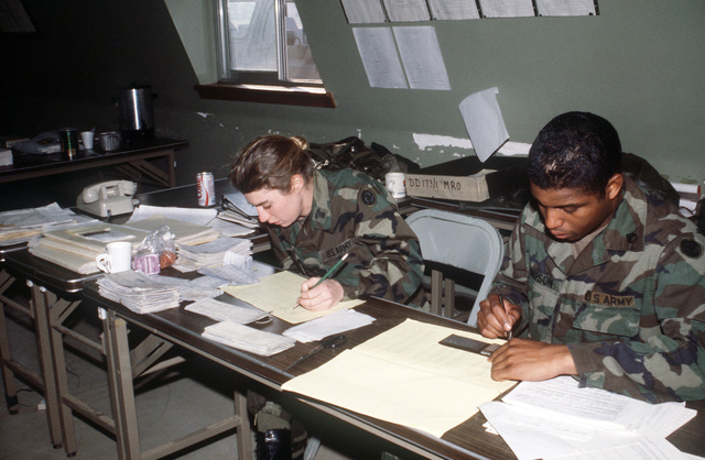 Staff Sergeant (SSG) Simpson and First Lieutenant (1LT) Giula Giacoppe, left, I Corps, work on redeployment schedules at the redeployment center at the conclusion of the joint US/South Korean Exercise TEAM SPIRIT '87