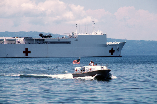 A motor launch from the hospital ship USNS MERCY (T-AH-19), background, makes its way to shore. The recently outfitted Military Sealift Command ship is visiting various ports in the Philippines during the first phase of its five-month humanitarian medical service and training mission. While in the Philippines, U.S. Navy, Army and Air Force medical personnel embarked aboard the MERCY are providing treatment for indigent Filipinos, both ashore and aboard ship