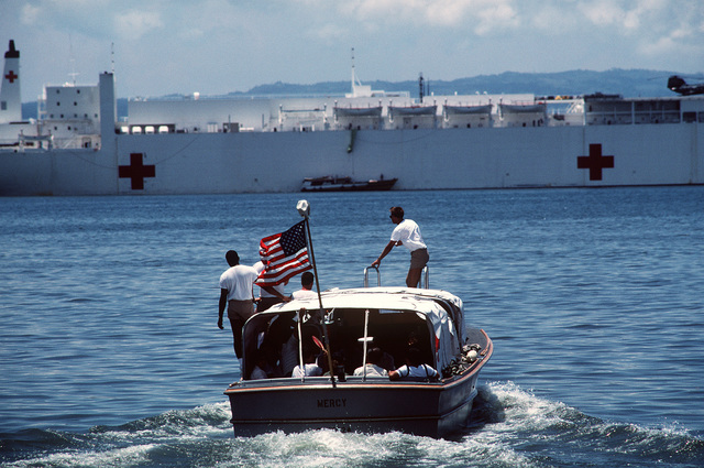 A motor launch from the hospital ship USNS MERCY (T-AH-19), background, transports local Filipinos back to the ship. The recently outfitted Military Sealift Command ship is visiting various ports in the Philippines during the first phase of its five-month humanitarian medical service and training mission. U.S. Navy, Army and Air Force medical personnel embarked aboard the MERCY are providing treatment for indigent Filipinos, both ashore and aboard ship