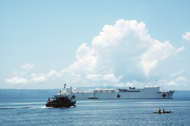 A Philippine patrol boat heads toward the hospital ship USNS MERCY (T-AH 19) anchored off the coast.  The recently outfitted Military Sealift Command ship is visiting various ports in the Philippines during the first phase of its five-month humanitarian medical service and training mission.  While in the Philippines, US Navy, Army and Air Force medical personnel embarked aboard the MERCY are providing treatment for indigent Filipinos, both ashore and aboard ship