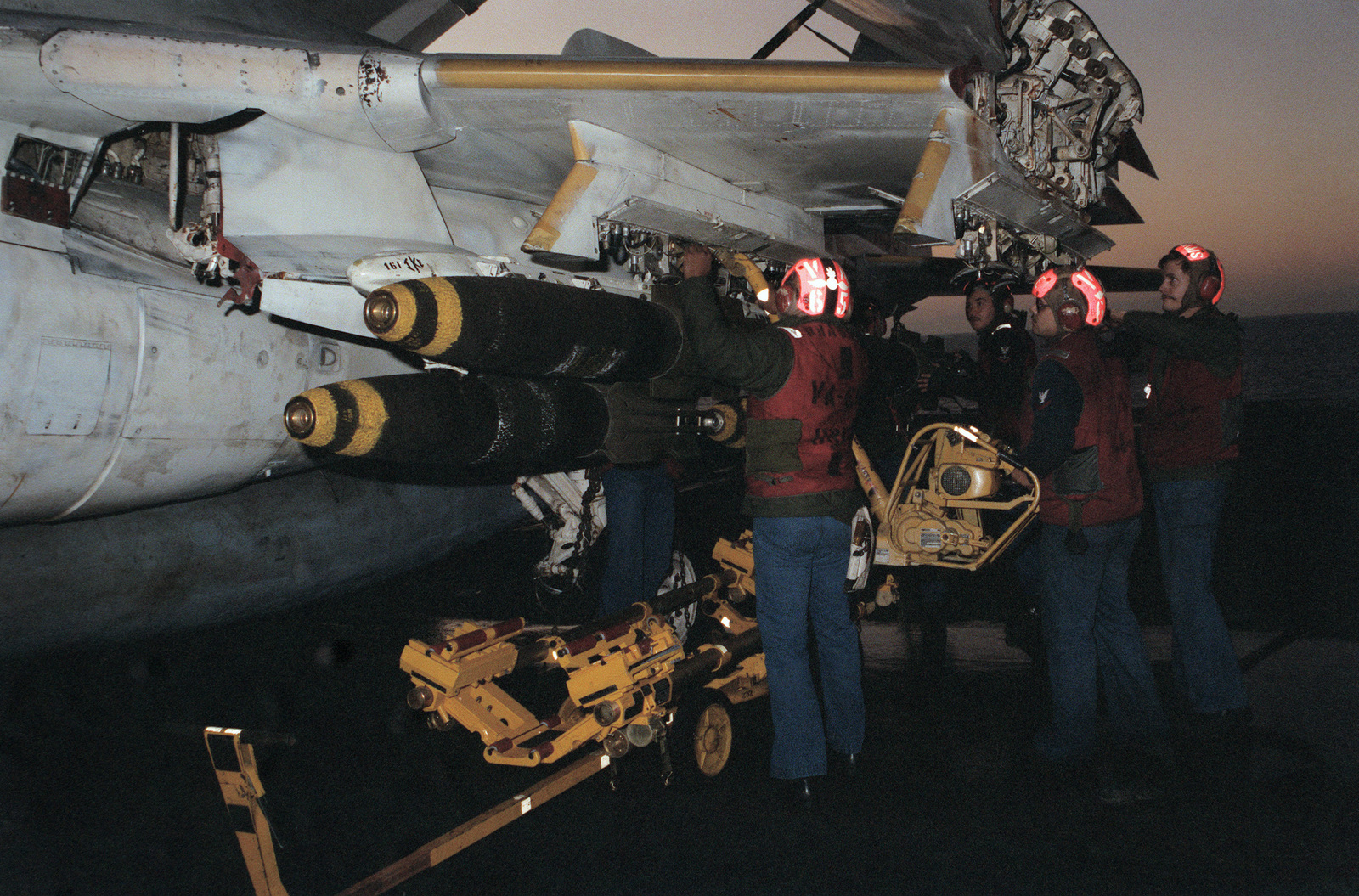 Attack Squadron 65 (VA-65) aviation ordnancemen attach Mark 82 500-pound retarded delivery bombs to the wing pylons of an A-6E Intruder aircraft during flight operations aboard the nuclear-powered aircraft carrier USS DWIGHT D. EISENHOWER (CVN 69)