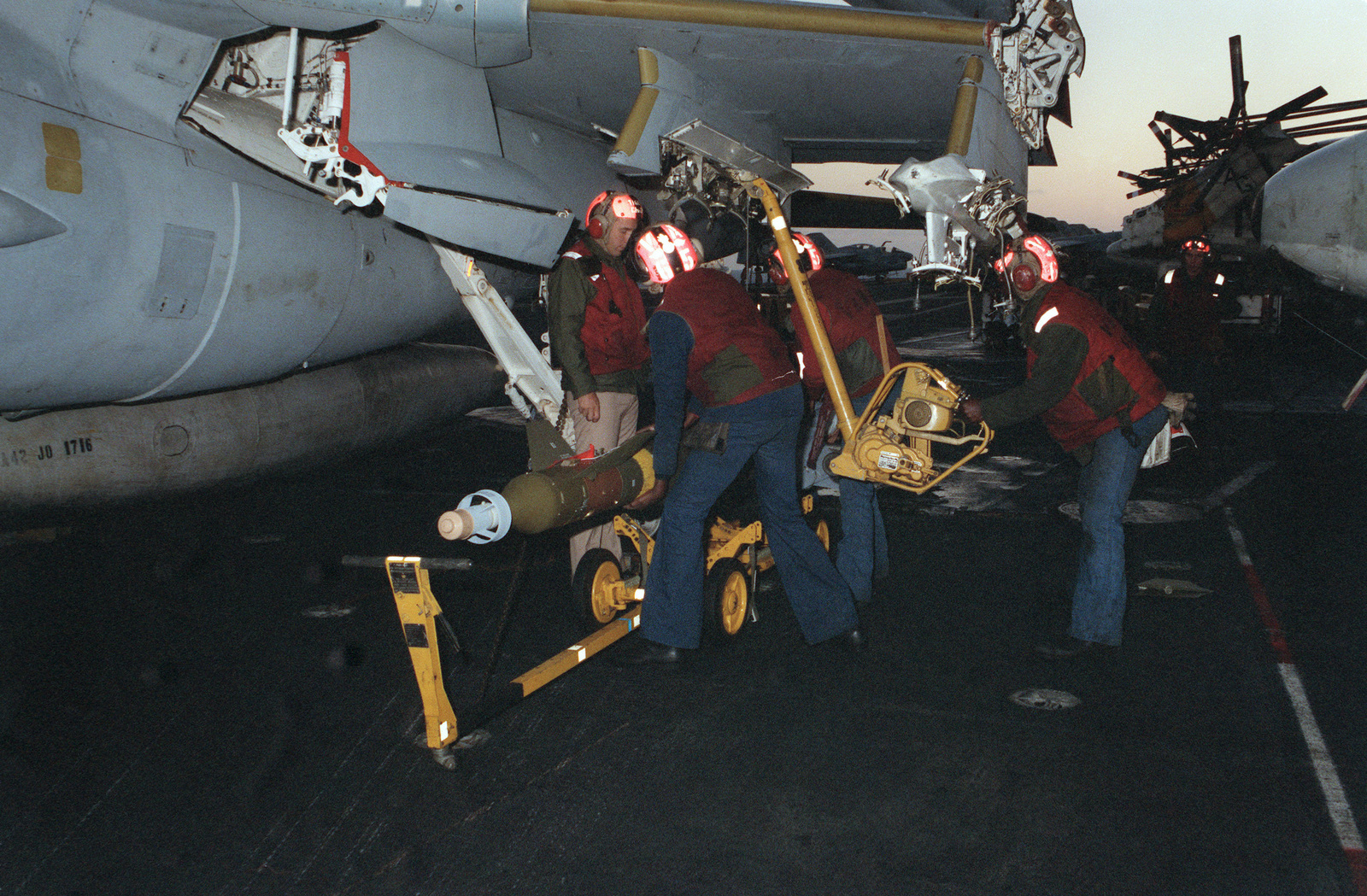 Attack Squadron 65 (VA-65) aviation ordnancemen position a Mark 84 laser-guided bomb under the wing pylon of an A-6E Intruder aircraft during flight operations aboard the nuclear-powered aircraft carrier USS DWIGHT D. EISENHOWER (CVN 69)