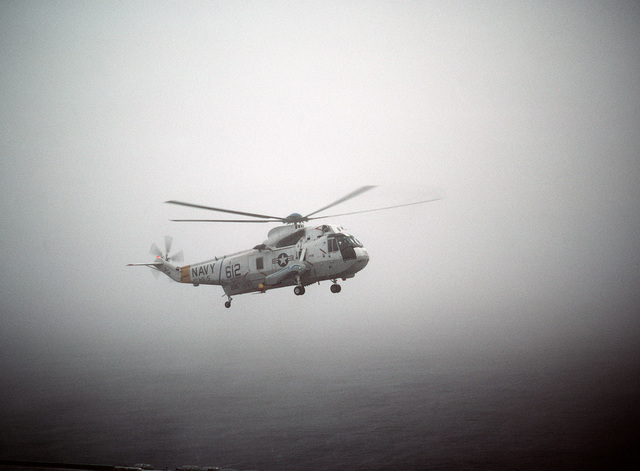 A Helicopter Anti-submarine Squadron 5 (HS-5) SH-3H Sea King helicopter approaches the stern of the nuclear-powered aircraft carrier USS DWIGHT D. EISENHOWER (CVN 69) for a landing in heavy fog.  Note:  First view in a series of six